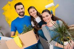 De gelukkige vader, de moeder en weinig dochter maken binnenshuis kleine vernieuwing voor het zetten van het op verkoop royalty-vrije stock foto