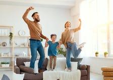 De gelukkige vader van de familiemoeder en kinddochter die thuis dansen stock foto