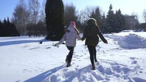 De gelukkige van de familiemoeder en baby looppas van de meisjesdochter, gang het spelen in de winter in openlucht in de sneeuw stock footage