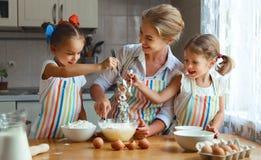 De gelukkige van familiemoeder en kinderen tweelingen bakken binnen het kneden deeg Royalty-vrije Stock Afbeeldingen