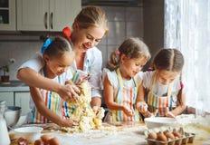 De gelukkige van familiemoeder en kinderen tweelingen bakken binnen het kneden deeg Stock Afbeelding