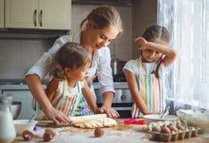 De gelukkige van familiemoeder en kinderen tweelingen bakken binnen het kneden deeg Stock Afbeeldingen