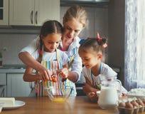 De gelukkige van familiemoeder en kinderen tweelingen bakken binnen het kneden deeg Royalty-vrije Stock Afbeelding