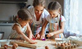 De gelukkige van familiemoeder en kinderen tweelingen bakken binnen het kneden deeg Stock Fotografie