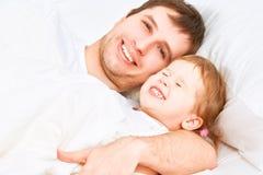 De gelukkige van het familievader en kind slaap van de babydochter in bed Stock Afbeelding