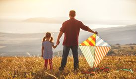 De gelukkige van het familievader en kind vlieger van de dochterlancering op weide royalty-vrije stock foto's
