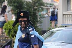 De gelukkige ventilator van de touristervoetbal in nationale Russische militaire de winterhoed met kokarde hoed-ushanka royalty-vrije stock afbeeldingen