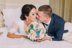 De gelukkige vermoeide jonggehuwden leggen op bed in hotelruimte na huwelijksviering en aandeelkus Stock Afbeelding