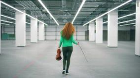 De gelukkige violist loopt in bureauruimte, houdend een viool en een strijkstok stock footage
