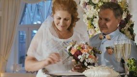 De gelukkige volwassen bruid ondertekent een huwelijksakte stock footage