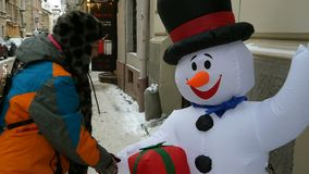 De gelukkige volwassen vrouw speelt en heeft pret met een decoratieve sneeuwman stock videobeelden