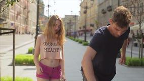De gelukkige vriend koestert zijn bekoord elegant meisje en toont het met een skateboard rijden in slo-mo stock video