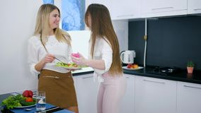 De gelukkige vrienden bekijken foto's op androïde met maaltijd in handen die zich in keuken bevinden stock footage