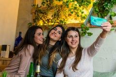 De gelukkige vrienden groeperen het drinken bier en het nemen selfie bij het restaurant van de brouwerijbar stock afbeeldingen