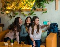 De gelukkige vrienden groeperen het drinken bier en het nemen selfie bij het restaurant van de brouwerijbar royalty-vrije stock foto