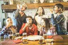 De gelukkige vrienden groeperen het eten van pizza bij het huis van het chaletrestaurant royalty-vrije stock afbeeldingen
