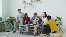 De gelukkige vrienden hebben partij en thuis het zingen samen terwijl hun vriend het spelen gitaar stock footage