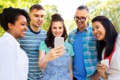 De gelukkige vrienden met smartphone bij de zomer parkeren stock afbeelding