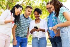 De gelukkige vrienden met smartphones bij de zomer parkeren royalty-vrije stock afbeeldingen