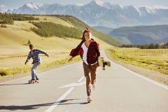 De gelukkige vrienden met vleten en longboards hebben pret stock afbeelding