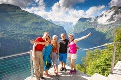 De gelukkige vrienden ontspannen op Geiranger-fjord De mensen genieten van goed weer in Noorwegen stock fotografie