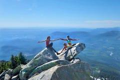 De gelukkige vrienden op berg bereiken samen het hebben van pret een hoogtepunt stock foto's