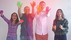 De gelukkige vrienden werpen de verf rechtstreeks van handen aan de camera terwijl status in studio dichtbij witte muur 3840x2160 stock videobeelden