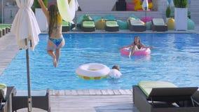 De gelukkige vrienden in de zomer voegen samen, ontspant de jonge vrouwen in poolside en meisje met opblaasbare ringensprongen na stock videobeelden