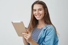 De gelukkige vriendschappelijke schitterende vrouwelijke hulp klaar hulp beantwoordt uit klantenvragen glimlachend ruim het houde stock fotografie
