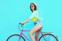 De gelukkige vrij jonge vrouw berijdt een fiets over kleurrijke blauwe achtergrond Royalty-vrije Stock Foto