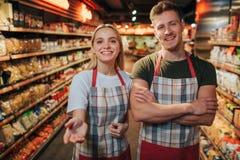 De gelukkige vrolijke jonge man en de vrouw bevinden zich in kruidenierswinkelopslag onder deegwaren shelfs Zij stellen op camera royalty-vrije stock afbeeldingen