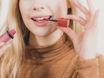 De gelukkige vrolijke vrouw die lippen gebruiken polijst royalty-vrije stock foto