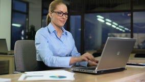 De gelukkige vrouw beëindigt project op laptop, verlatend bureau, succesvolle werkdag stock video