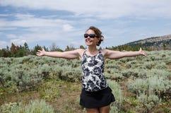 De gelukkige vrouw bevindt zich op een gebied van hoge van de woestijnalsem en creosoot struiken in landelijk Wyoming royalty-vrije stock fotografie