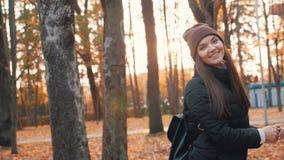 De gelukkige vrouw in de daling van het de herfstpark gaat omhoog weg De gouden Herfst stock video