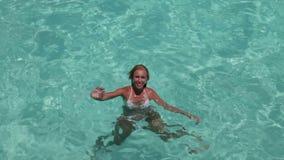 De gelukkige vrouw in de overzeese golven aan ons die een hand begroeten Royalty-vrije Stock Afbeelding
