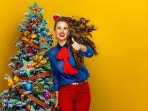 De gelukkige in vrouw dichtbij Kerstboom het tonen beduimelt omhoog Stock Afbeeldingen