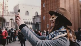 De gelukkige vrouw die een modieuze hoed en een wit Carnaval-gezichtsmasker dragen neemt selfie foto glimlachend bij de stadsvier stock video
