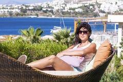 De gelukkige vrouw die van de zomervakantie het leggen genieten sunbed in een tropische tuin Stock Afbeeldingen