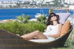 De gelukkige vrouw die van de zomervakantie het leggen genieten sunbed in een tropische tuin Royalty-vrije Stock Foto