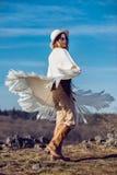 De gelukkige vrouw die van het land van aard in bergen genieten die poncho dragen stock foto's