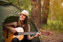 De gelukkige vrouw die van de reizigerslevensstijl op vakantie met tent het spelen gitaar in bos kamperen stock afbeeldingen