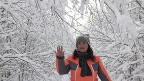 De gelukkige vrouw die van de de winterdag in het hout witte sneeuwbos lopen wat betreft tak van bomen, sneeuw die van hen vallen stock video