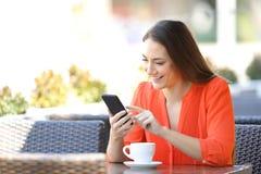 De gelukkige vrouw doorbladert een smartphone in een koffiewinkel stock afbeeldingen