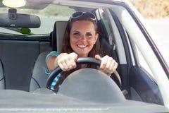 De gelukkige vrouw drijft een auto Stock Afbeeldingen