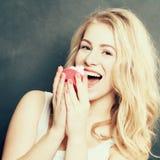 De gelukkige vrouw eet cake Stock Foto's