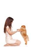 De gelukkige vrouw en haar mooie kleine rode hondspitz over witte achtergrond sluiten portret stock foto