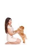 De gelukkige vrouw en haar mooie kleine rode hondspitz over witte achtergrond sluiten portret stock afbeelding