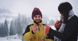 De gelukkige vrouw en de man ge?mponeerd van de plaats die zij en zij hebben gevonden verrukt drinken wat hete thee van ijzerkop  stock footage