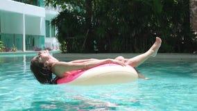 De gelukkige vrouw en opblaasbaar zwemt ring in vorm van een doughnut in de pool stock videobeelden